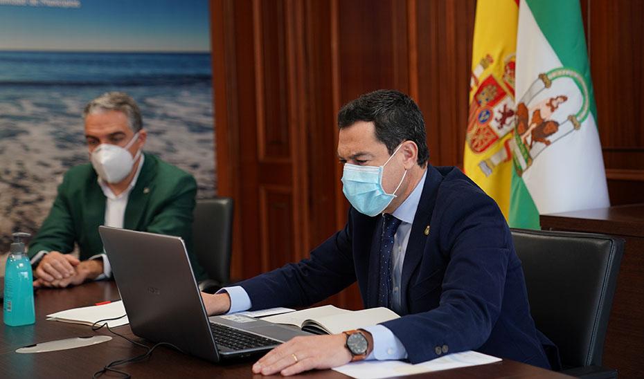 El presidente, Juanma Moreno, hablando por videoconferencia con los alcaldes costeros malagueños.